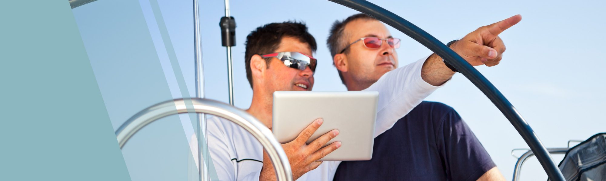 two men pointing from behind sailboat helm