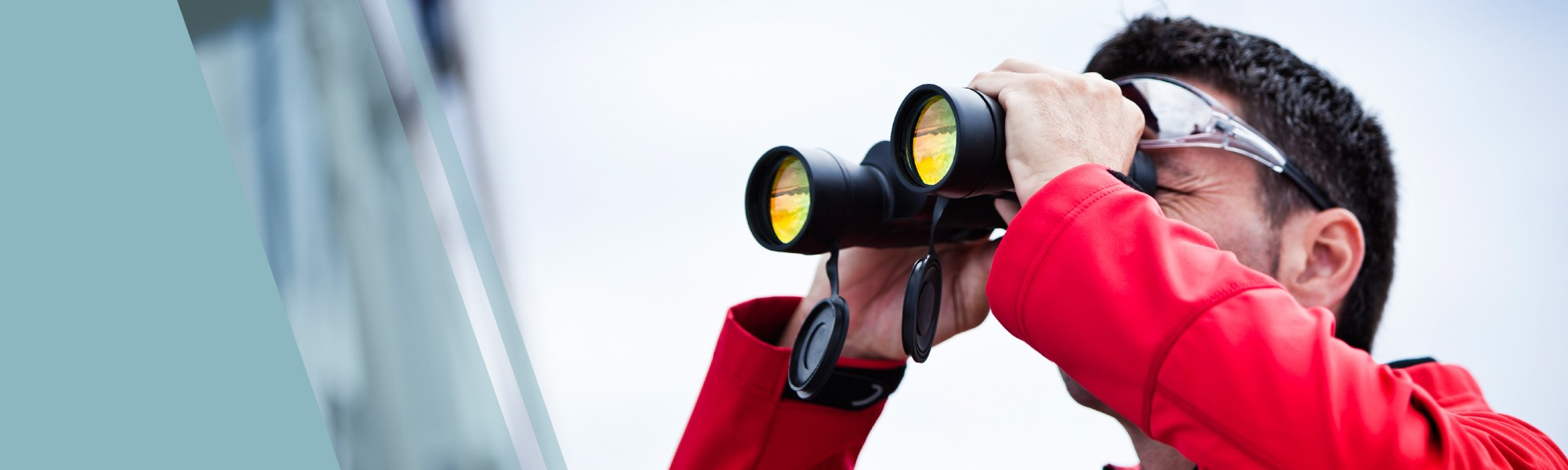 man looking through binoculars in red coat